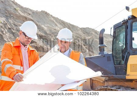 Engineers analyzing blueprint at construction site