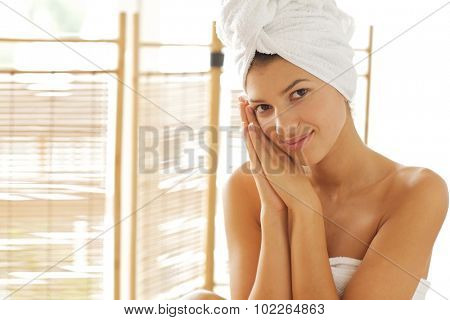 Portrait of young woman wrapped in towel with hands clasped