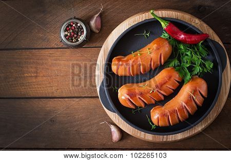 Sausages on the grill pan on the wooden background
