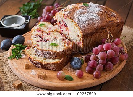 Juicy and tender cupcake with plums and grapes