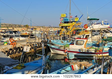 Girl fishing among fishing boats