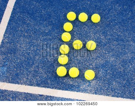Tennis ball in shape of letter E on a blue artificial grass