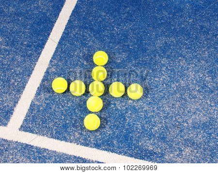 Tennis ball in shape of a Plus sign on a blue artificial grass
