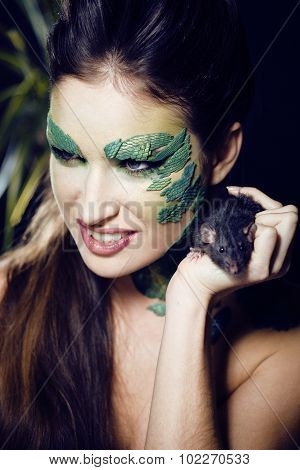 woman with creative make up like snake and rat in her hands, halloween horror closeup
