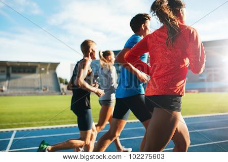 Young Athletes Running On Race Track In Stadium
