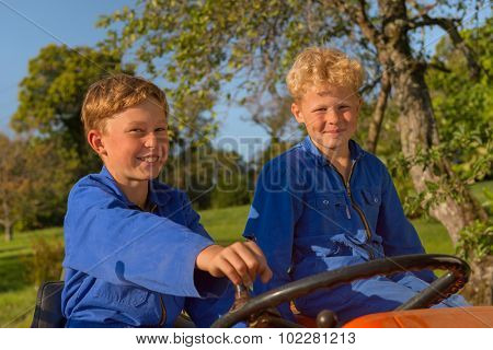 Farm boys riding on orange tractor