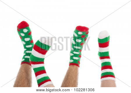 Many feet in Christmas socks isolated over white background