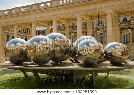 Silver balls in the fountain reflect courtyard of Palais Royal