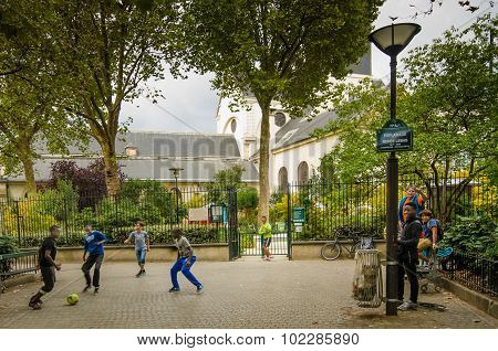 Boys play soccer in a Paris park