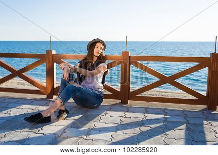 Gorgeous hipster girl rest outdoors while strolling along the seashore in spring season