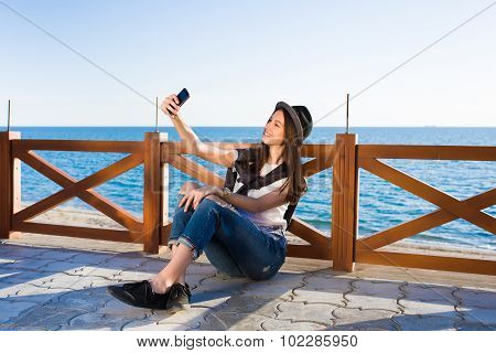 Young happy female hipster taking picture of herself on smart phone strolling on the beach