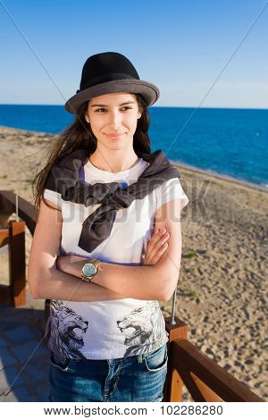 Stylish female posing for the camera while looking aside on the beach in sunny day