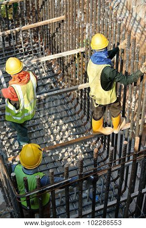Group of construction workers fabricating pile cap steel reinforcement bar
