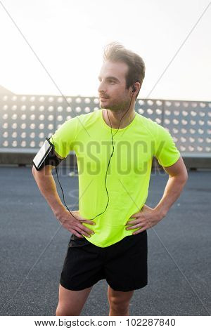 Half length portrait of a young person resting outdoors while getting ready to run