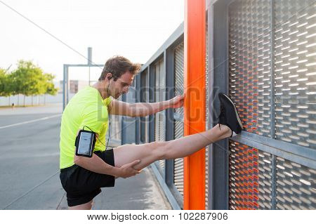 Young concentrated man doing legs exercises leaning on a metal fence at sunny day