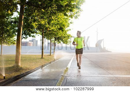 Male sports structure runs outdoors in sunny morning while using modern device
