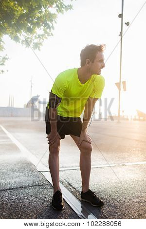 Exhausted male runner rests with hands on knees while listening to music in headphones