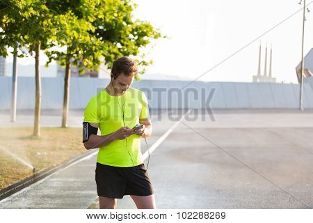 Caucasian male runner using technology with copy space area for text message