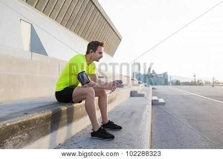 Young sports man holding bottle of water while taking break after an active run outdoors