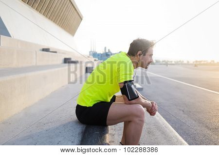 Young sports build man listening to music in headphones while resting after early morning run