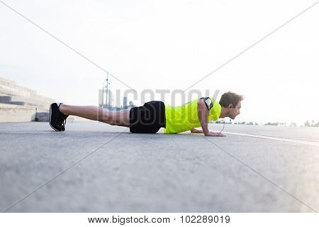 Young male jogger warm up before start his workout training outside