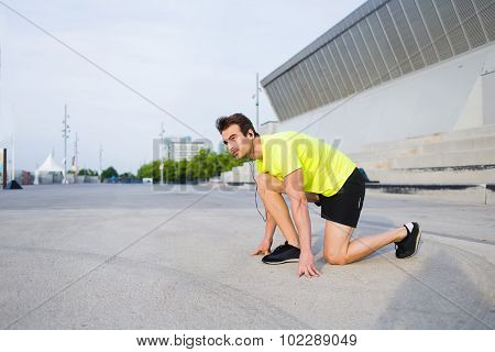 Male runner listening to music in headphones while warm up before start his morning jog