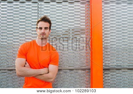 Portrait of handsome sport build man standing against metal fence looking confident with hands cross