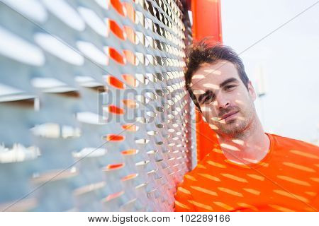 Portrait of tired male runner leaning on metal fence thoughtful looking to the camera