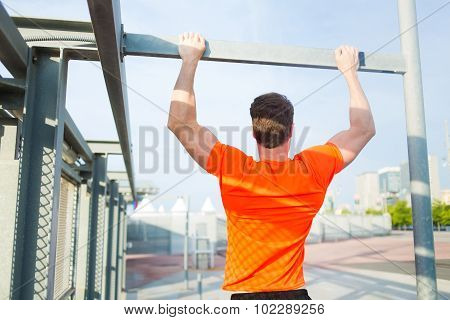 Young male runner in bright t-shirt training hard in urban setting at sunset