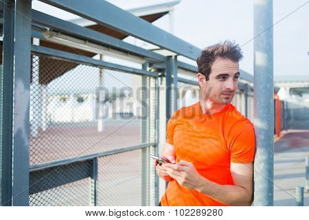Young sports man using mobile phone while rest after workout outdoors