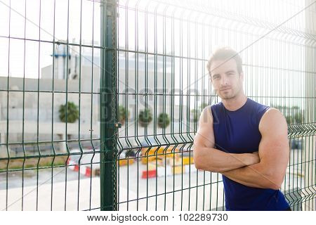 Handsome young athlete man taking break after workout outside in summer