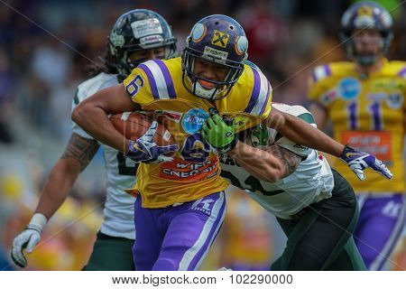 VIENNA, AUSTRIA - JUNE 22, 2014: WR Laurinho Walch (#6 Vikings) is tackled by CB Christian Kober (#31 Dragons).
