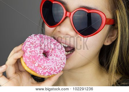 Sexy woman with red lolita glasses eating donut