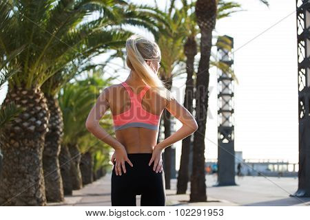 Young beautiful fit woman having rest after physical exercise