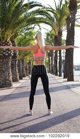 Fit woman dressed in sportswear doing physical exercises in the fresh air in beautiful park