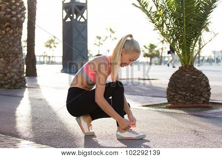 Happy fit woman taking break after workout outdoors in sunny summer day