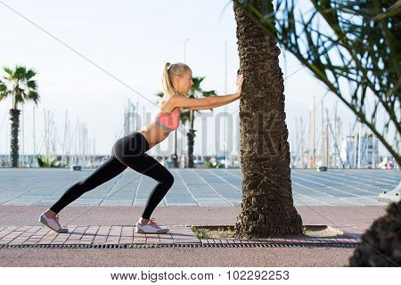 Healthy fit woman with perfect body stretching outdoors in summer day