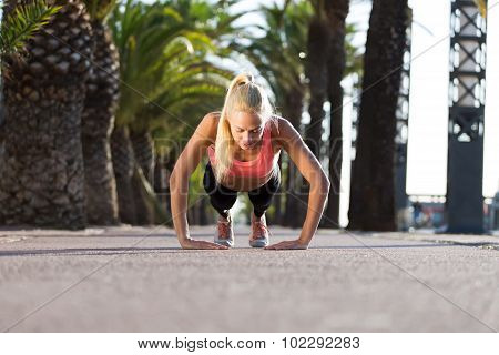 Young caucasian woman doing press ups in tropic urban setting with palm trees