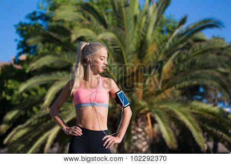 Female jogger with closed eyes enjoying sunny day and rest after workout