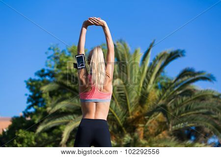 Young female jogger with running armband on the arm working out outdoors in sunny summer day