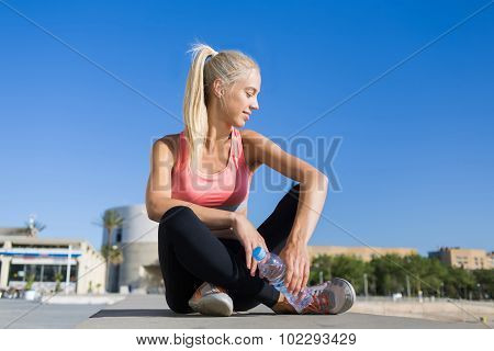 Young fit woman in sportswear taking break after run