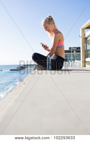 Young female runner using smart phone while resting training outdoors