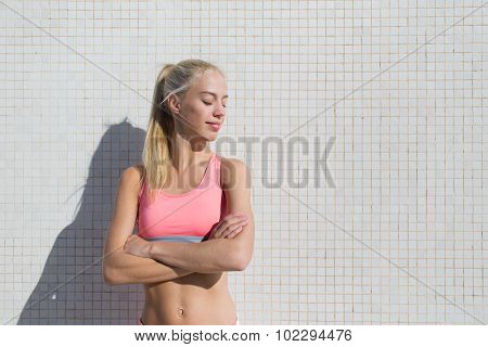 Female runner relaxing after morning jog in sunny summer day