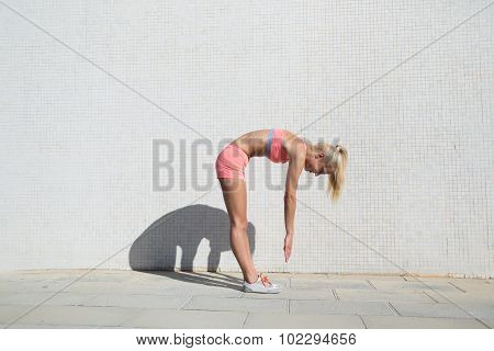 Young fit woman working out outdoors in sunny summer day