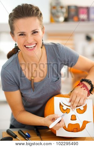 Happy Young Woman Using Stencils To Carve Pumpkin Jack-o-lantern