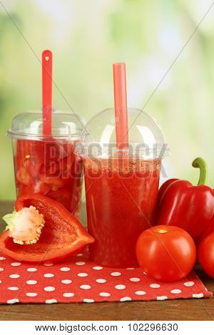 Red vegetable and fruit salad and healthy fresh drink in plastic cups on wooden background. Colorful diet concept
