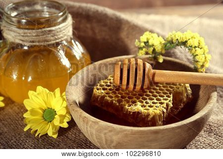 Pot of honey, honeycomb and dipper in bowl on sackcloth