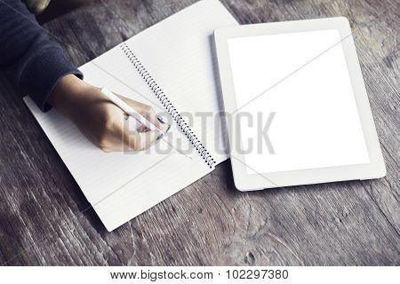 Girl Writes In A Notebook Lying Beside A Blank Digital Tablet