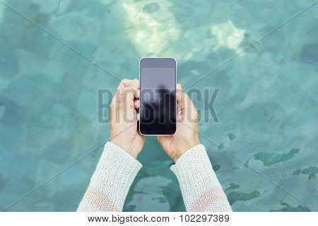 Girl Holding A Blank Cell Phone On The Background Of Water