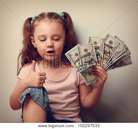 Happy Kid Girl Holding Money And Thinking How Many Dollar I Earned And Showing Thumb Up Sign